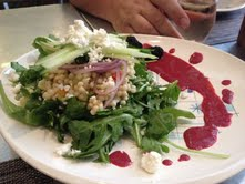 Arugula with Israeli couscous, goat cheese, lemon cucumber, and a blackberry yogurt dressing.