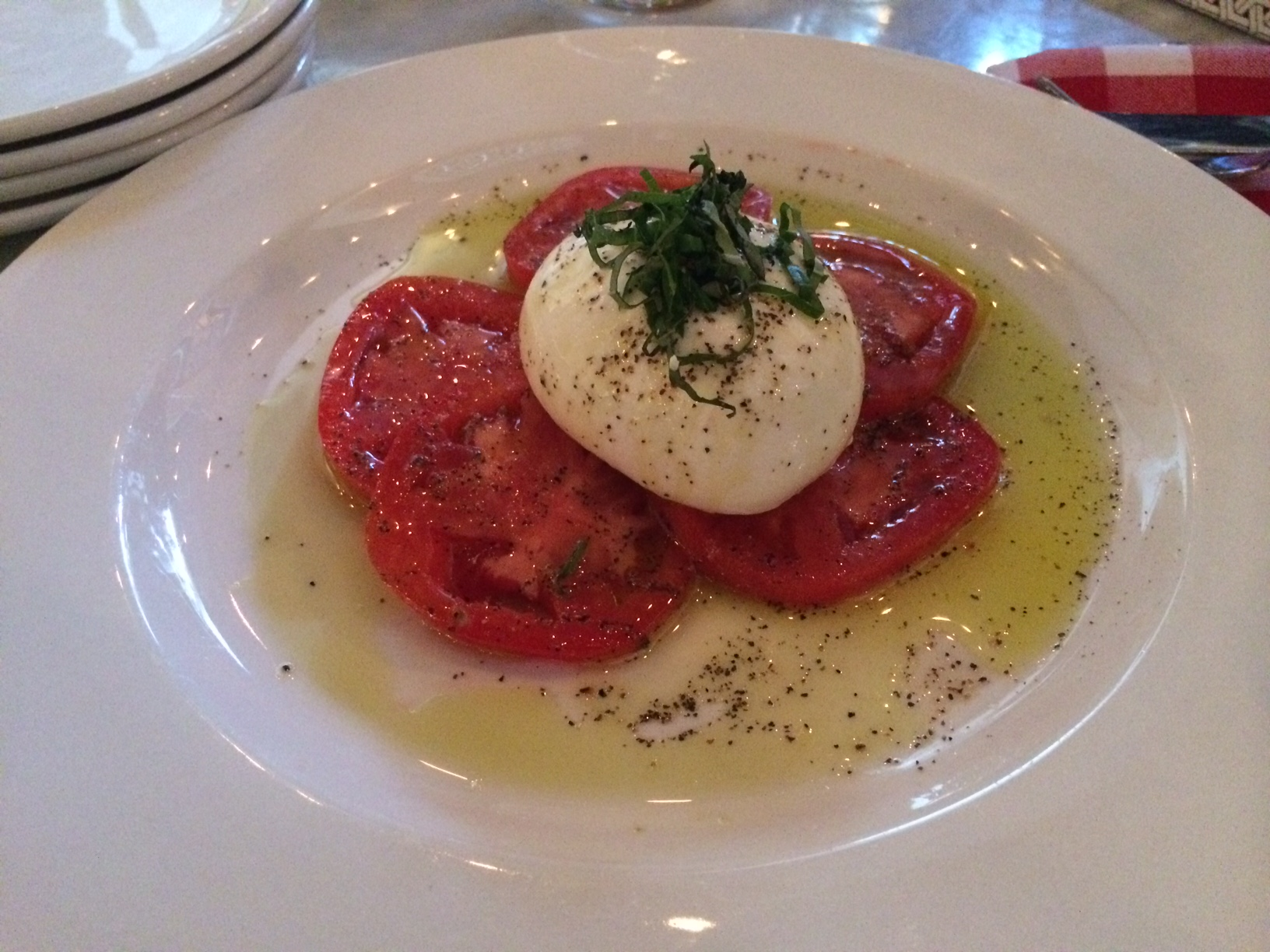 the traditional caprese salad is made even better at roslina with burrata cheese